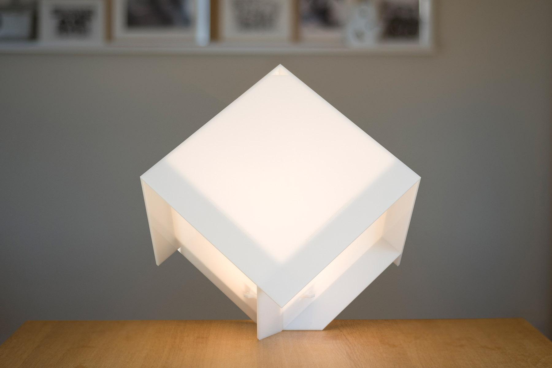 Lampe cubique sur une pointe, allumée